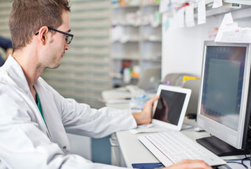 Lab technician using computer and tablet.