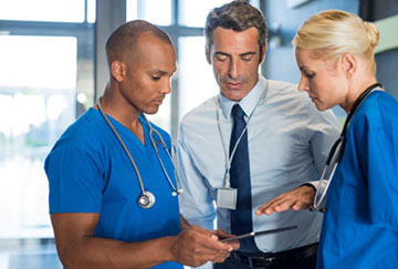 Two nurses and a c-suite looking at a tablet