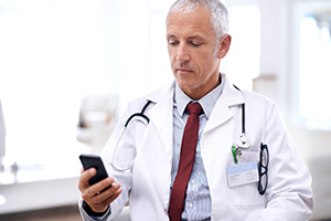 Physician looking at smartphone